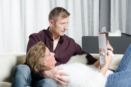 kanapa: couple is reading a magazine on couch