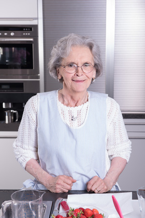 preparing: Female Senior preparing Strawberries