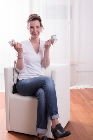 counting money: woman sitting in armchair and counting money is happy