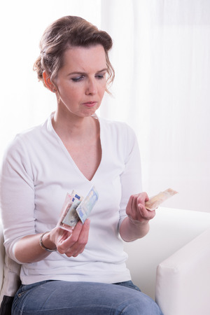 golden ager: woman sitting in armchair and counting money Stock Photo