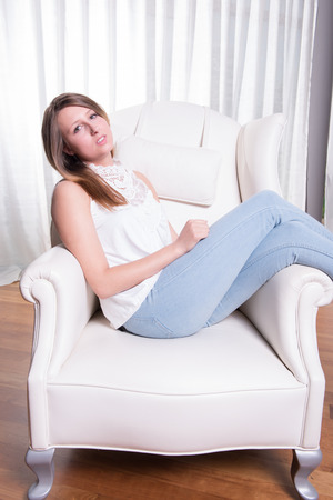 hanging around: young woman hanging around in armchair Stock Photo
