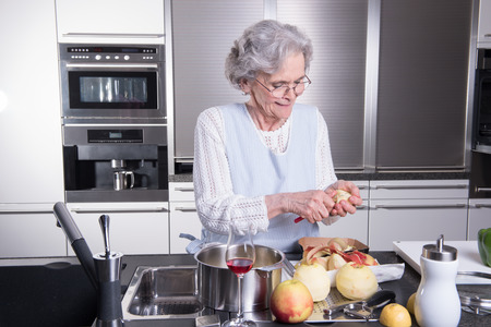 active female senior peeling apple in the kitchen