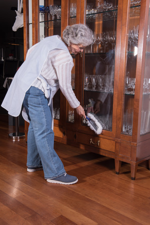 causcasian: active female senior is cleaning furniture