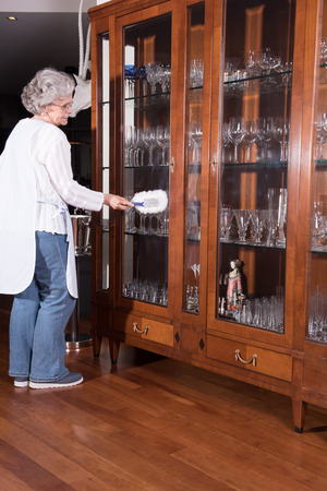 active female senior is cleaning furniture