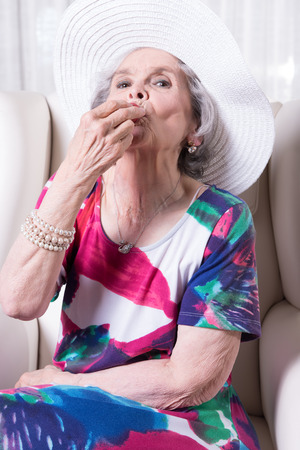 senior eating: active female senior eating strawberry