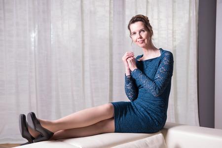 Donna attraente in abito blu seduto sul divano