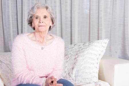actief luisteren: actieve vrouwelijke senior ontspannen op de bank luisteren