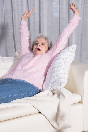 kanapa: active female senior stretching on couch