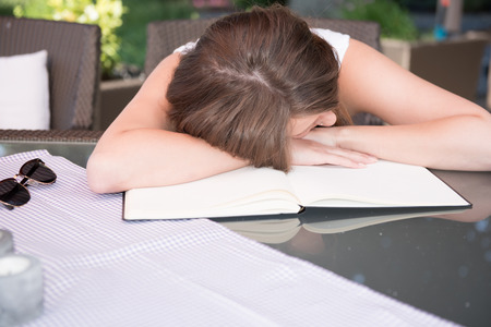 workbook: attractive young girl is sleeping on workbook Stock Photo