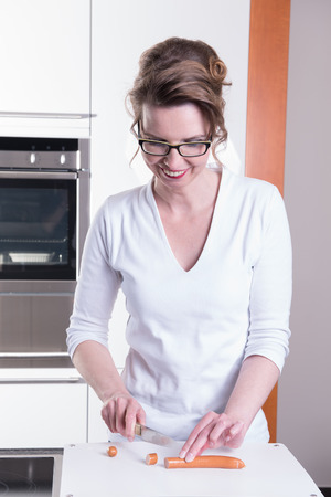 ktchen: attractive woman in modern ktchen cutting sausage Stock Photo
