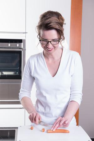 attractive woman in modern ktchen cutting sausage Stock Photo