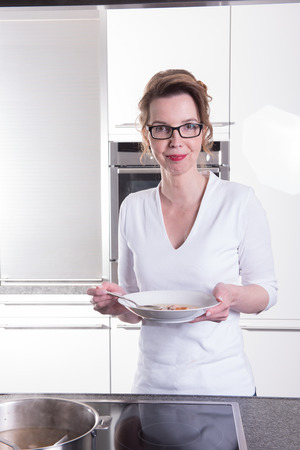 attractive woman in modern ktchen cooking and eating soup