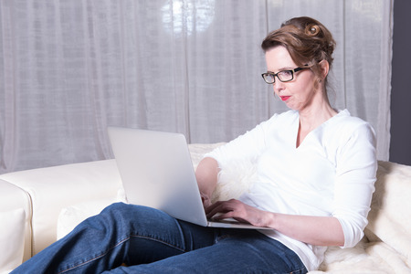 woman couch: attractive woman working on computer on couch