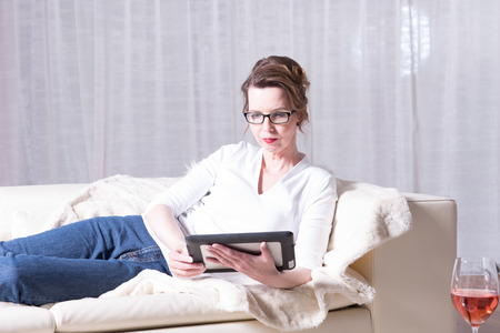 woman couch: attractive woman reading on tablet on couch