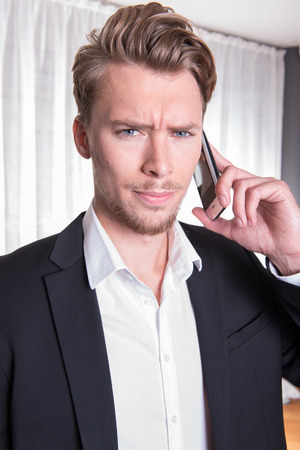 phonecall: portrait angry young business man in suit on the phone