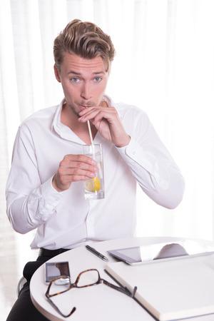 rubia ojos azules: joven hombre de negocios que tiene un vaso de agua