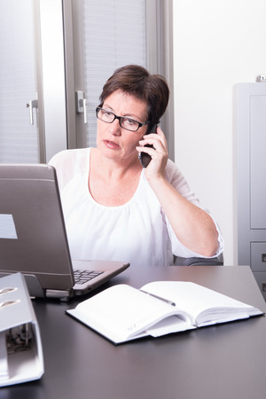 homeoffice: woman in her homeoffice on the phone
