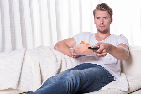 blonde blue eyes: Portrait young man sitting on couch and eating chips and zapping TV Stock Photo