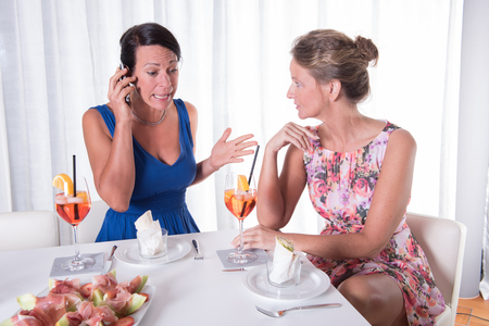 phonecall: two attractive women - one is concerned about phone call