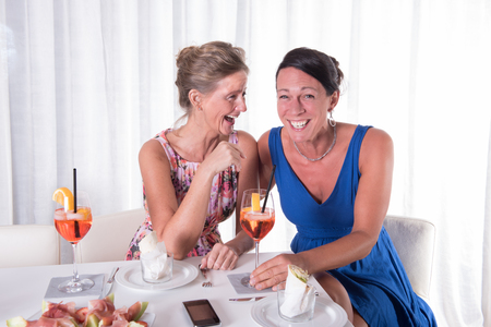 phonecall: two attractive women giggeling together Stock Photo