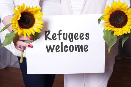 refugees: two female helpers welcome refugees Stock Photo