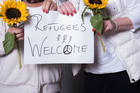 welcome people: female helpers welcome refugees Stock Photo
