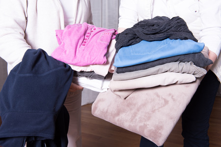 helpers: female helpers offer warm clothes to refugees