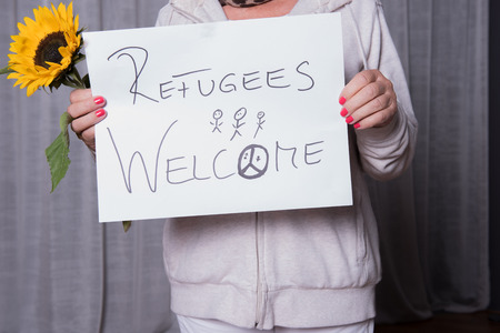 war refugee: female helper welcomes refugees
