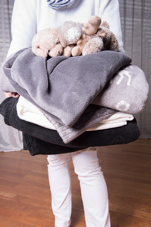 welcome to: female helper welcomes refugees with warm blankets for cold nights Stock Photo