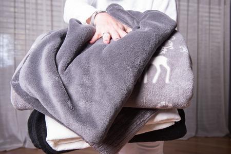 catarro: ayudante femenina da la bienvenida a los refugiados con mantas de abrigo para las noches fr�as Foto de archivo