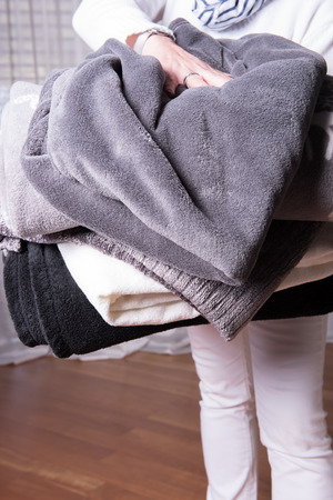 nights: female helper welcomes refugees with warm blankets for cold nights Stock Photo