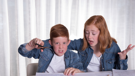 annoyed: two kids are annoyed doing their homework