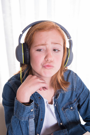 ist: young redhaired girl ist listening with headphones