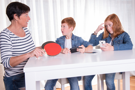 child sport: two redhaired kids are playing with their smartphones- mother wants them to do sports