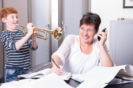 disturbing: mother is working in home office, son is disturbing by playing the trumpet Stock Photo