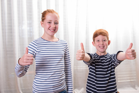 sripes: brother and sister smiling and having thumbs up