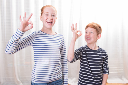 sripes: brother and sister smiling and showing everything is fine Stock Photo