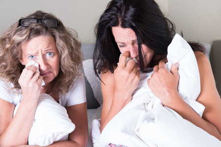 beautiful crying woman: two attractive women sitting in bed and crying Stock Photo