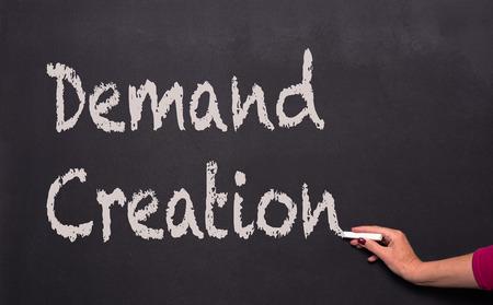 demand: womans hand with chalk on blackboard writing demand creation