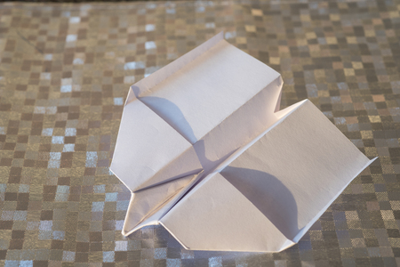 paper plane: folded white paper plane on a silver patterned background
