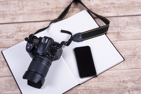Photographers workplace with book, phone  and camera on wooden table