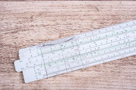 rule: historic slide rule lying on wooden table Stock Photo