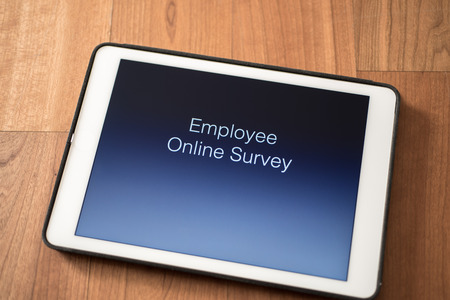 tablet on table with online employee survey Standard-Bild