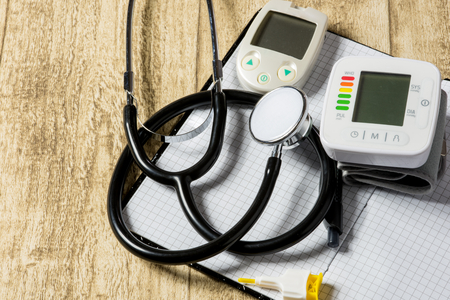 blood sugar: stethoskope on wooden desk with blood pressure measurement copy space Stock Photo