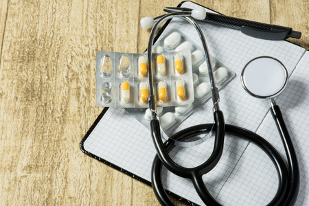 stethoskope: stethoskope on wooden desk with pills, pencil and notebook, copy space Stock Photo