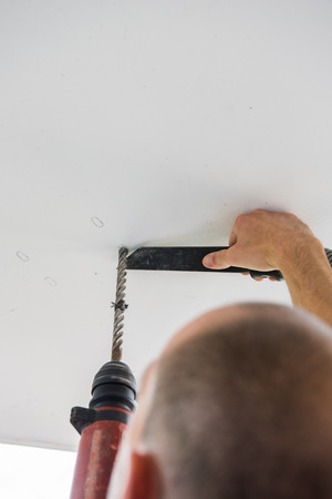 drilling machine: man is drilling holes into concrete ceiling with drilling machine Stock Photo