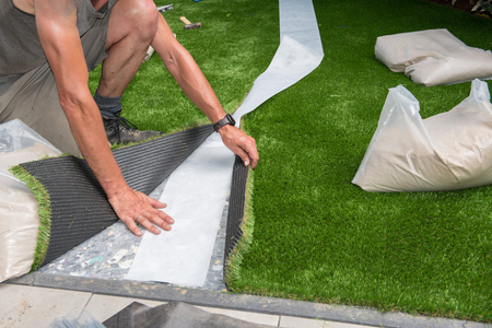 professional gardener is cutting artificial turf to fit