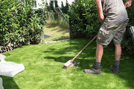 professionele tuinman zet zand op kunstgras Stockfoto