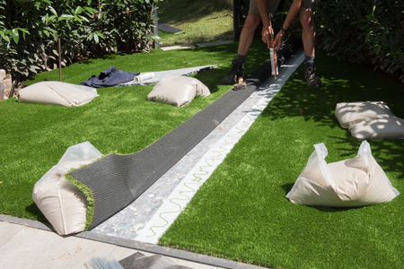 professional gardener is glueing artificial turf to fit