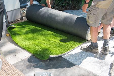 jardiniers professionnels déploient le gazon artificiel
